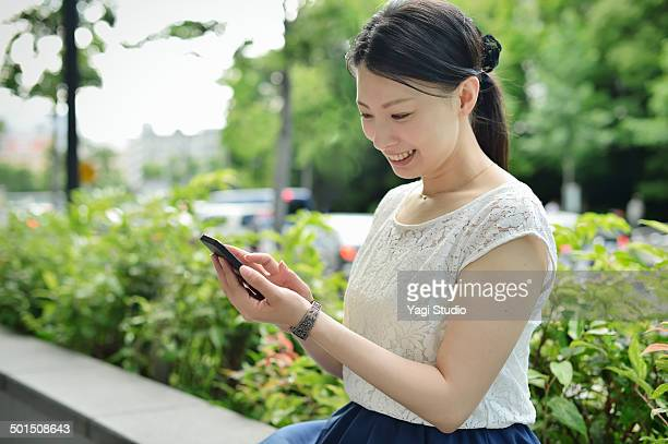 woman using smartphone in urban park - short sleeved stock pictures, royalty-free photos & images