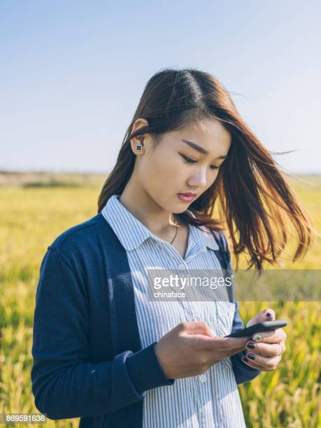 woman using smartphone in wheat field