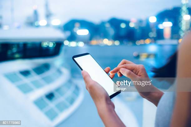 woman using smartphone next to a cruise by the victoria harbour at sunset - crucero vacaciones fotografías e imágenes de stock