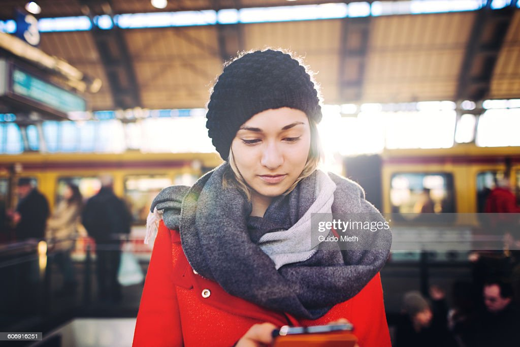 Woman using smartphone on a train station. : Stock Photo