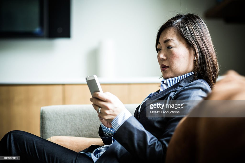 woman using smartphone on couch : Stock Photo