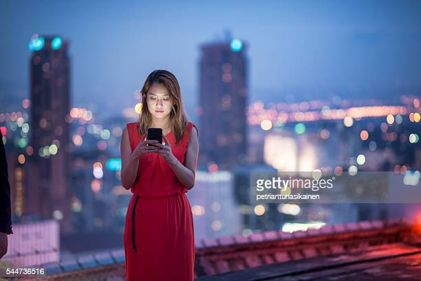 Woman using smartphone on rooftop.