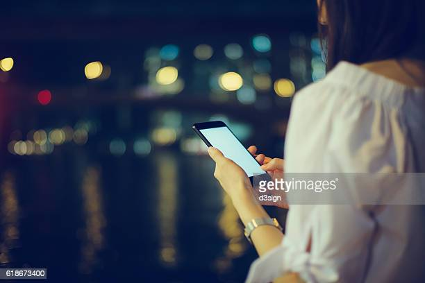 Woman using smartphone on the street at night