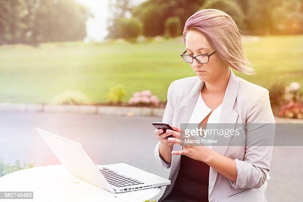 woman using smartphone outdoors - cavan images foto e immagini stock