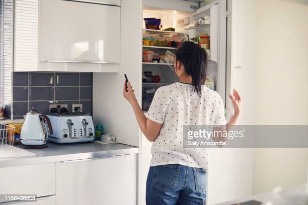 woman using smartphone - refrigerator stock pictures, royalty-free photos & images