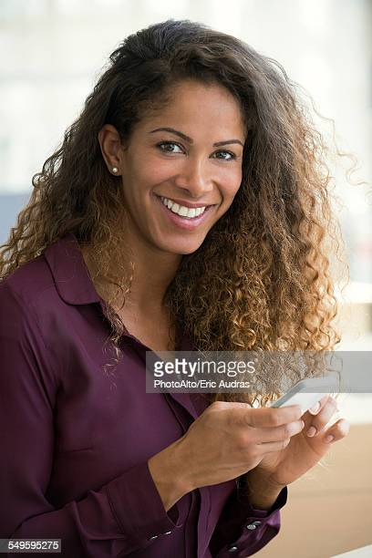 Woman using smartphone, smiling, portrait