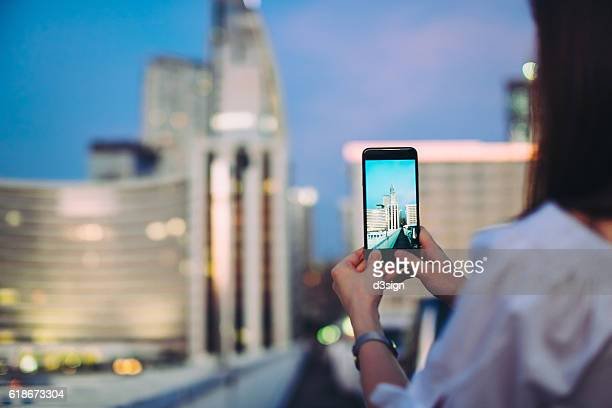 Woman using smartphone to capture city scene at night