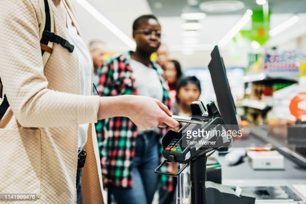 woman using smartphone to pay for groceries - contactless payment stock pictures, royalty-free photos & images