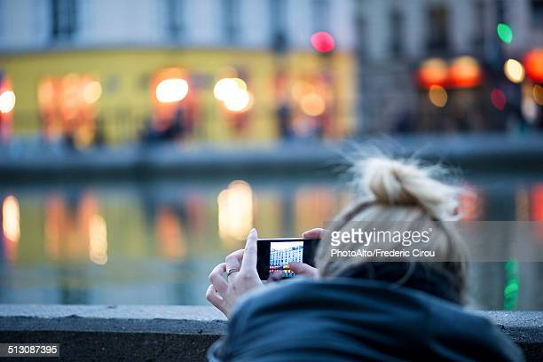 Woman using smartphone to photograph city scene