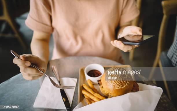 Woman using smartphone while having meal in a restaurant