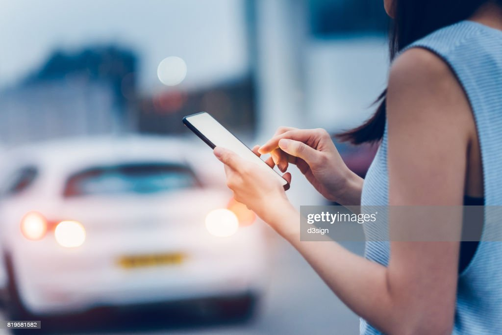 Woman using smartphone while waiting for a taxi ride on city street : Foto de stock