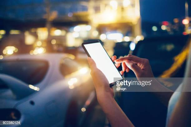Woman using smartphone while walking in outdoor car park at night