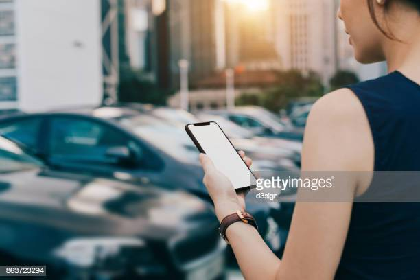 Woman using smartphone while walking to her car in outdoor car park in city