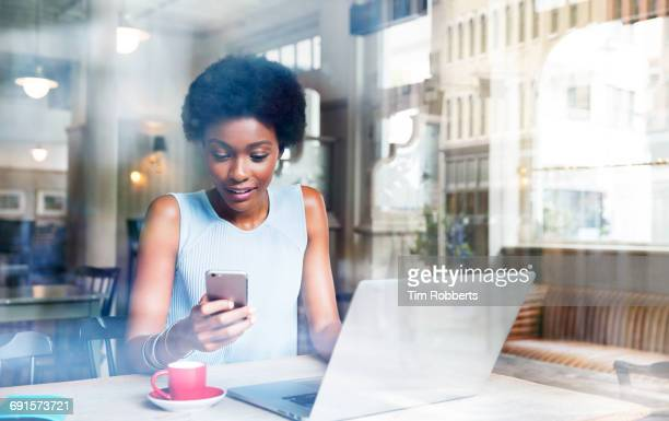 Woman using smartphone with laptop in cafe
