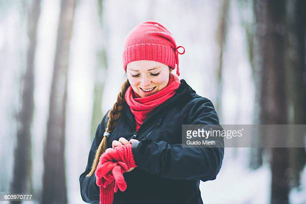 Woman using smartwatch in winterly forest.