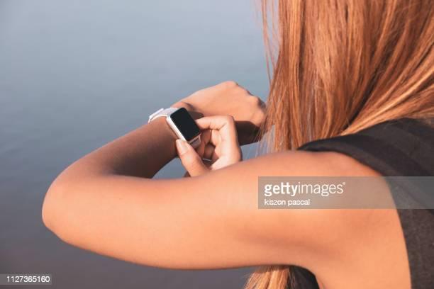 woman using smartwatch outdoors . - kleine uhr stock-fotos und bilder