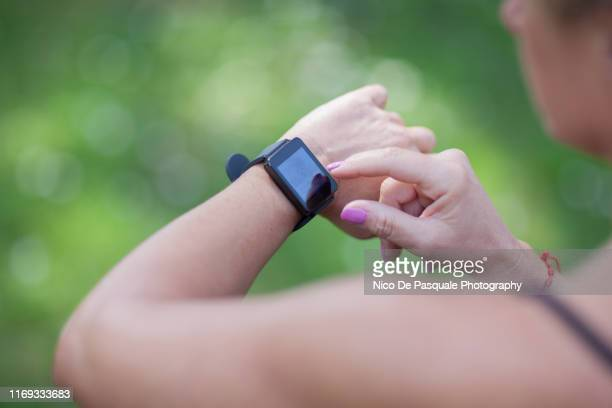 woman using smartwatch - nico de pasquale photography stock pictures, royalty-free photos & images