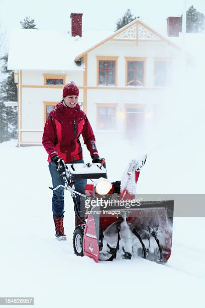 Woman using snowblower in front of house