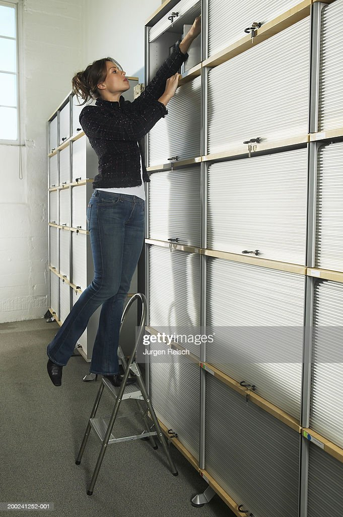 Woman using step stool to reach files : Stock-Foto