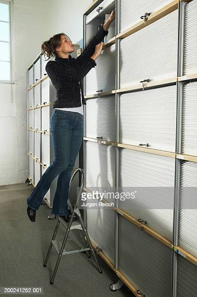 woman using step stool to reach files - vertikal stock-fotos und bilder