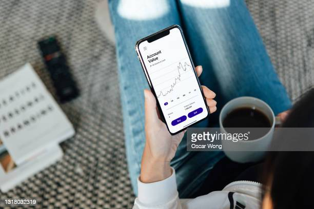 woman using stock trading app on mobile phone at home - stock price stock pictures, royalty-free photos & images