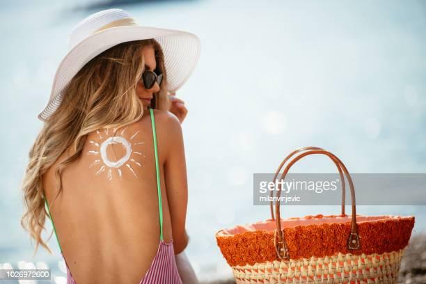 woman using sun cream on the beach - donne abbronzate foto e immagini stock