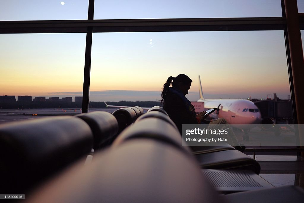 Woman using tablet at airport : Stock Photo