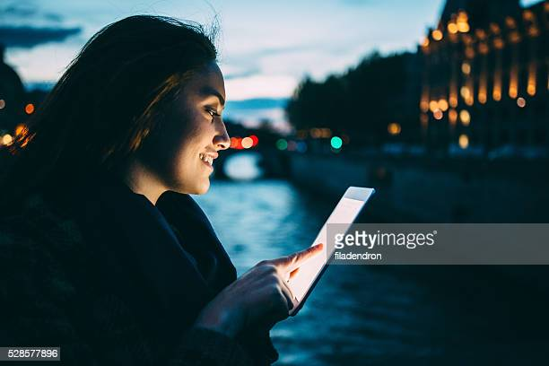 Woman using tablet at night