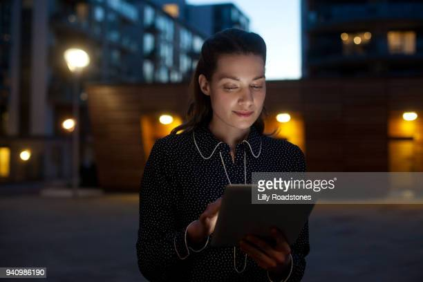 Woman using tablet computer at night