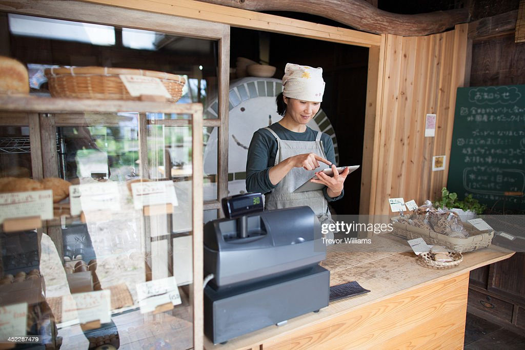 woman using tablet computer in asmall bakery : Stock Photo