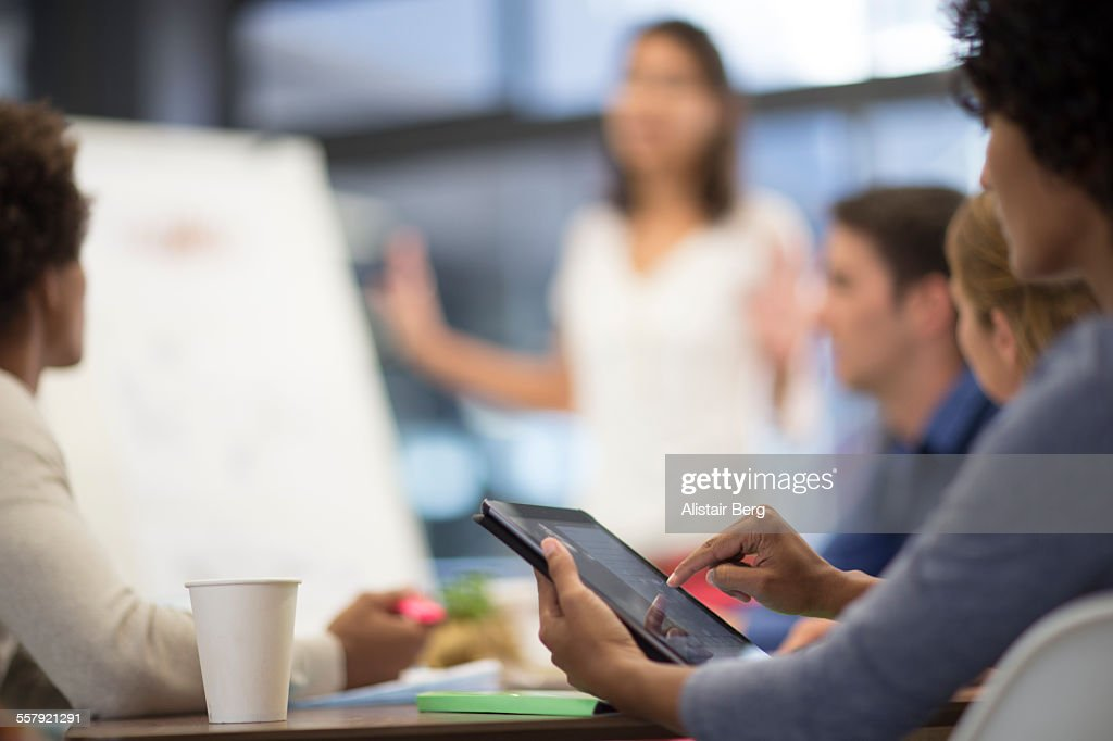 Woman using tablet computer in meeting : Stock Photo