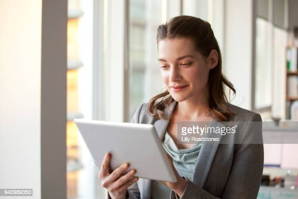 Woman using tablet computer in office