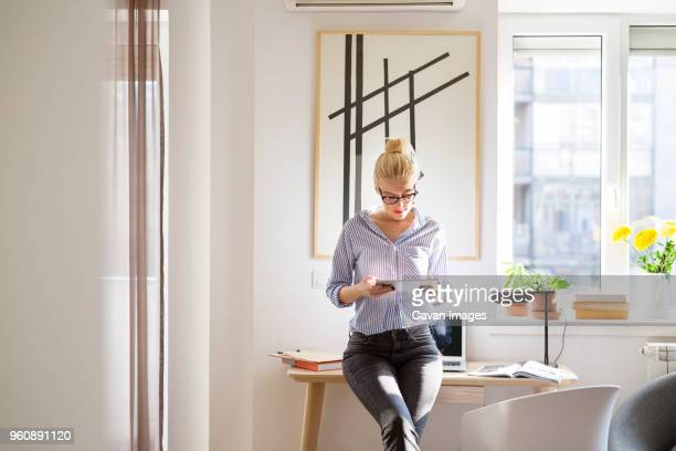 woman using tablet computer while leaning on table at home - donne di età media foto e immagini stock