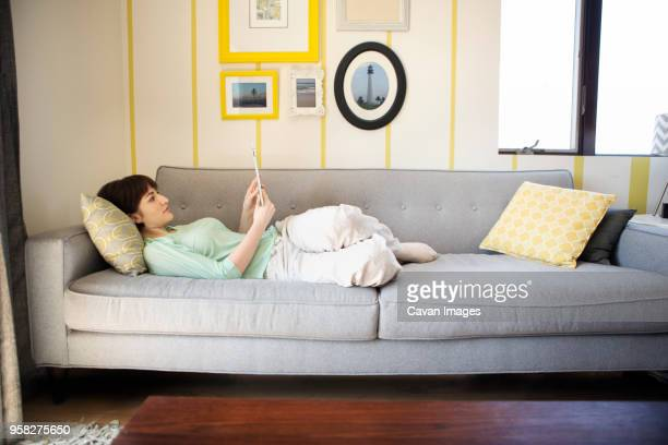 woman using tablet computer while lying on sofa at home - lying on front stock pictures, royalty-free photos & images