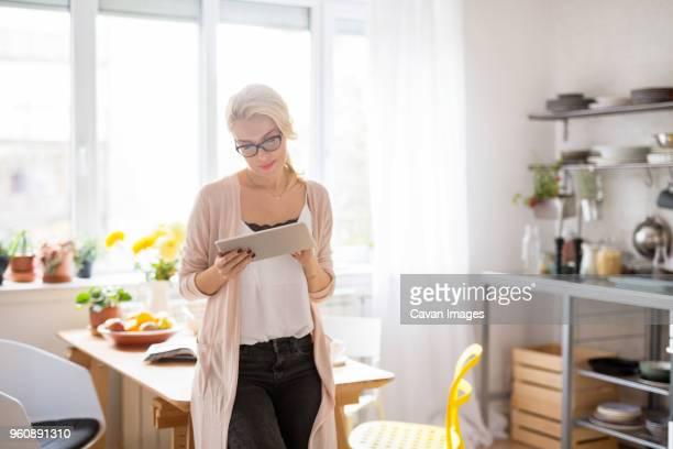 woman using tablet computer while standing at home - donne di età media foto e immagini stock
