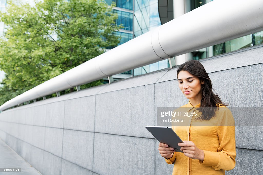 Woman using tablet in business district : Stock Photo