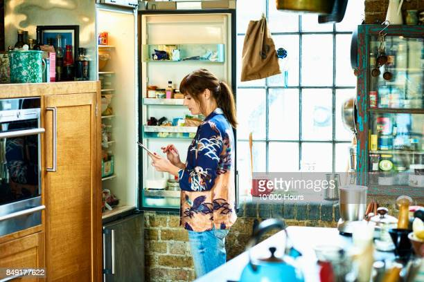 Woman using tablet in kitchen