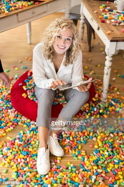 Woman using tablet in office surrounded by colorful polystyrene parts