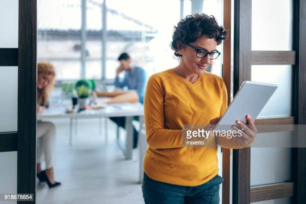 woman using tablet in the office - businesswear stock pictures, royalty-free photos & images