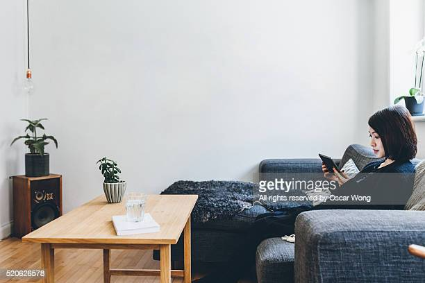 Woman using tablet on sofa at cozy home