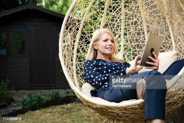 woman using tablet on swing seat in garden - mature women stock pictures, royalty-free photos & images