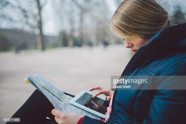 Woman using tablet pc and city map.