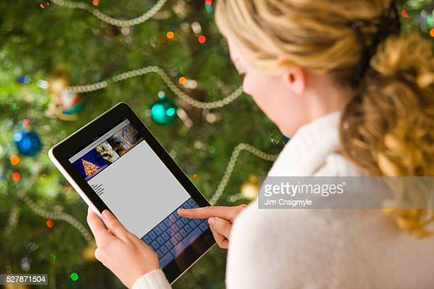 Woman using tablet pc by christmas tree
