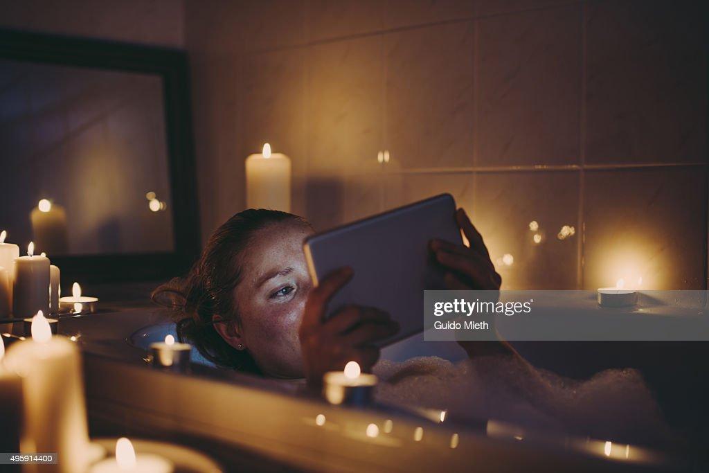 Woman using tablet pc in bathtub. : ストックフォト