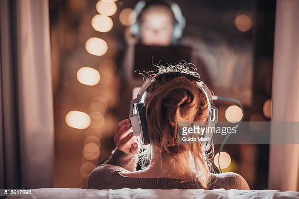 woman using tablet pc in evening. - listening stock pictures, royalty-free photos & images