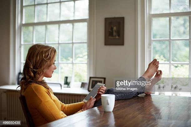Woman using tablet while relaxing in cottage