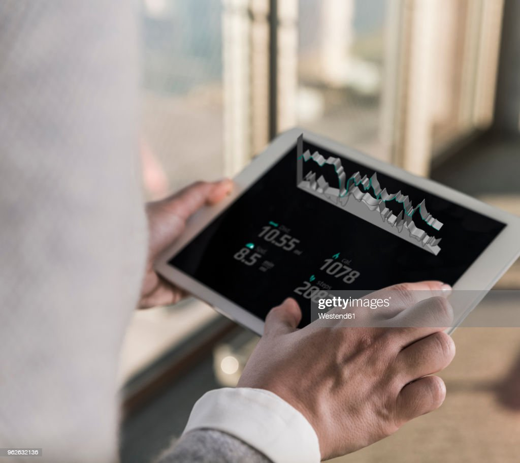 Woman using tablet with data emerging from screen : Stock Photo