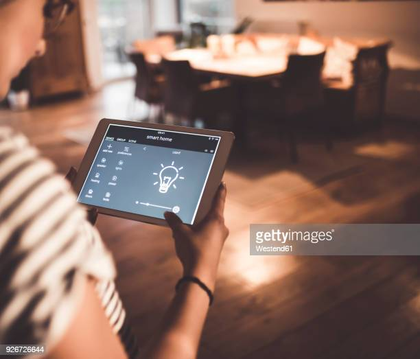 woman using tablet with smart home control functions at home - energy efficient stock pictures, royalty-free photos & images