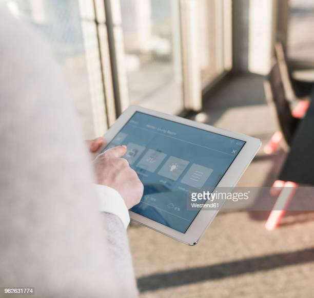 woman using tablet with smart home control functions in office - con eficaz consumo de energía fotografías e imágenes de stock