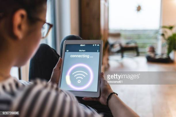 woman using tablet with wifi symbol at home - wireless technology foto e immagini stock